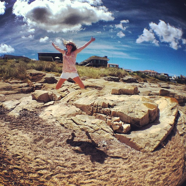Jenny jumping off beach rocks in Punta del Este